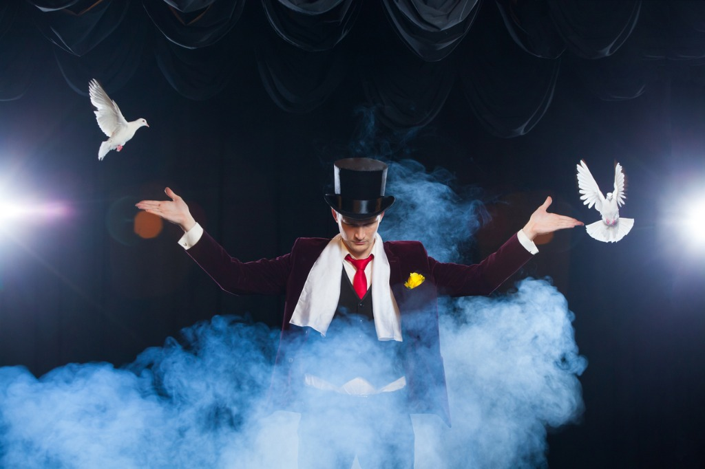 the-magician-with-a-two-flying-white-doves-on-a-black-background-in-picture-id882528002
